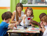 children-painting-together-with-nursery-teacher-in-a-kindergarten